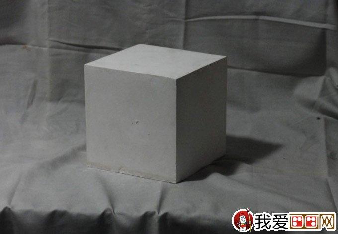石膏立方体素描教程原图的要求: 1、必须看到立方体的三个面,三个面大小要有区别,这是比较理想的角度,能很好的表现立方体形体特征。 2、单侧光源照射,使得三个面呈现黑(背光面)白(受光面)灰(测光面)有明显色调差异的三个面,这样不仅一目了然的认识三大面,而且在用调子塑造三个面的时候清晰简单。 3、衬布的色调应该区别于立方体三个面的色调,免得冲突,其次衬布摆放要有平面和立面的关系,这样使得画面有空间感,再次,衬布的布纹尽量简洁一些,不然就会显得碎。  石膏立方体素描教程步骤一:经营位置,模糊定形。面对一张白